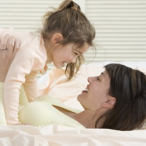 Mother and Daughter Playing on Bed