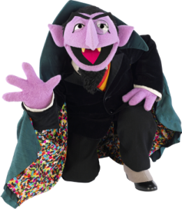"""Count von Count kneeling"" by Source. Licensed under Fair use via Wikipedia"