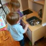 children play in toy kitchen