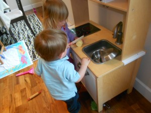 children play in toy kitchen